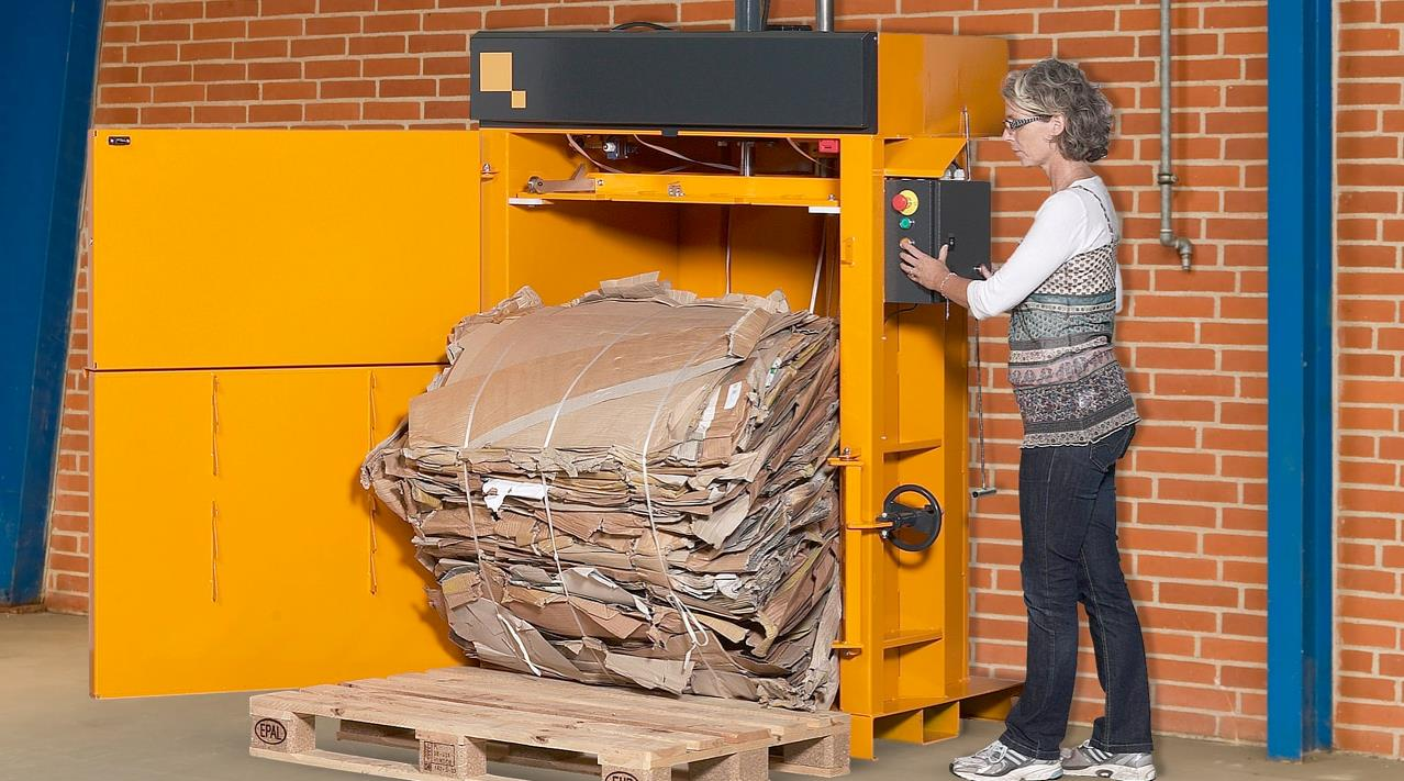 Woman ejects cardboard bale from Bramidan baler B5 Wide