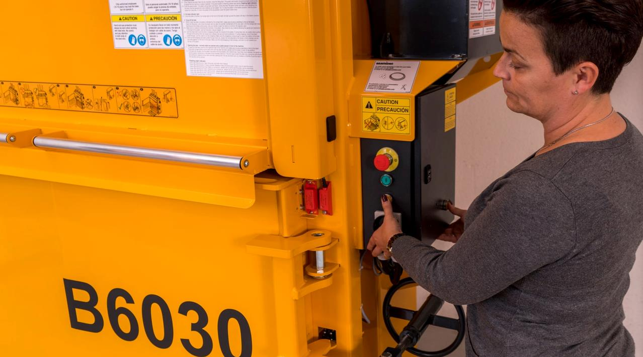 Woman uses safe two-hand ejection on Bramidan baler B6030