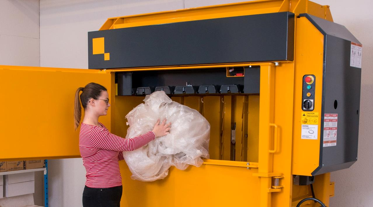 Girl fills plastic waste into Low Profile baler X6030 from Bramidan