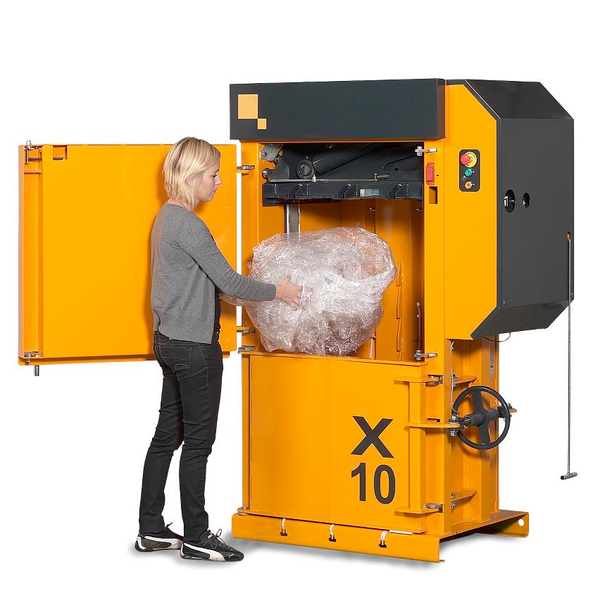 Women filling in plastic into yellow Bramidan baler X10