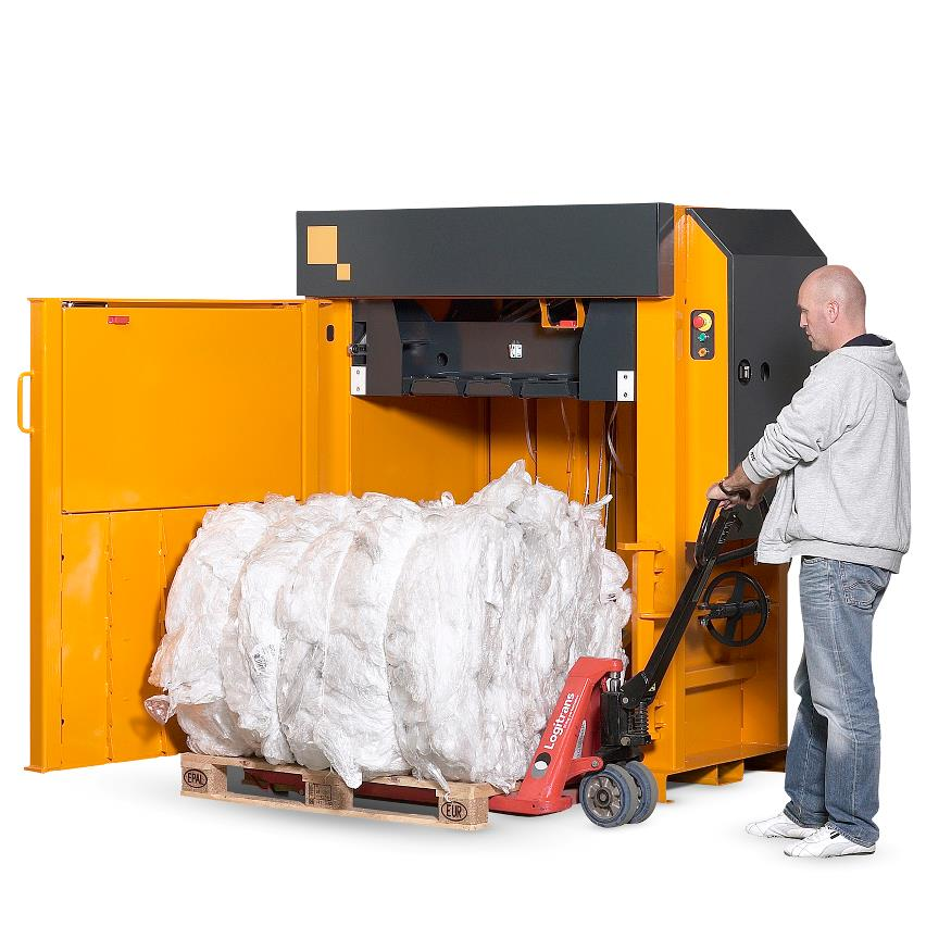 Man pulling plastic bale away on pallet jack from yellow Bramidan baler