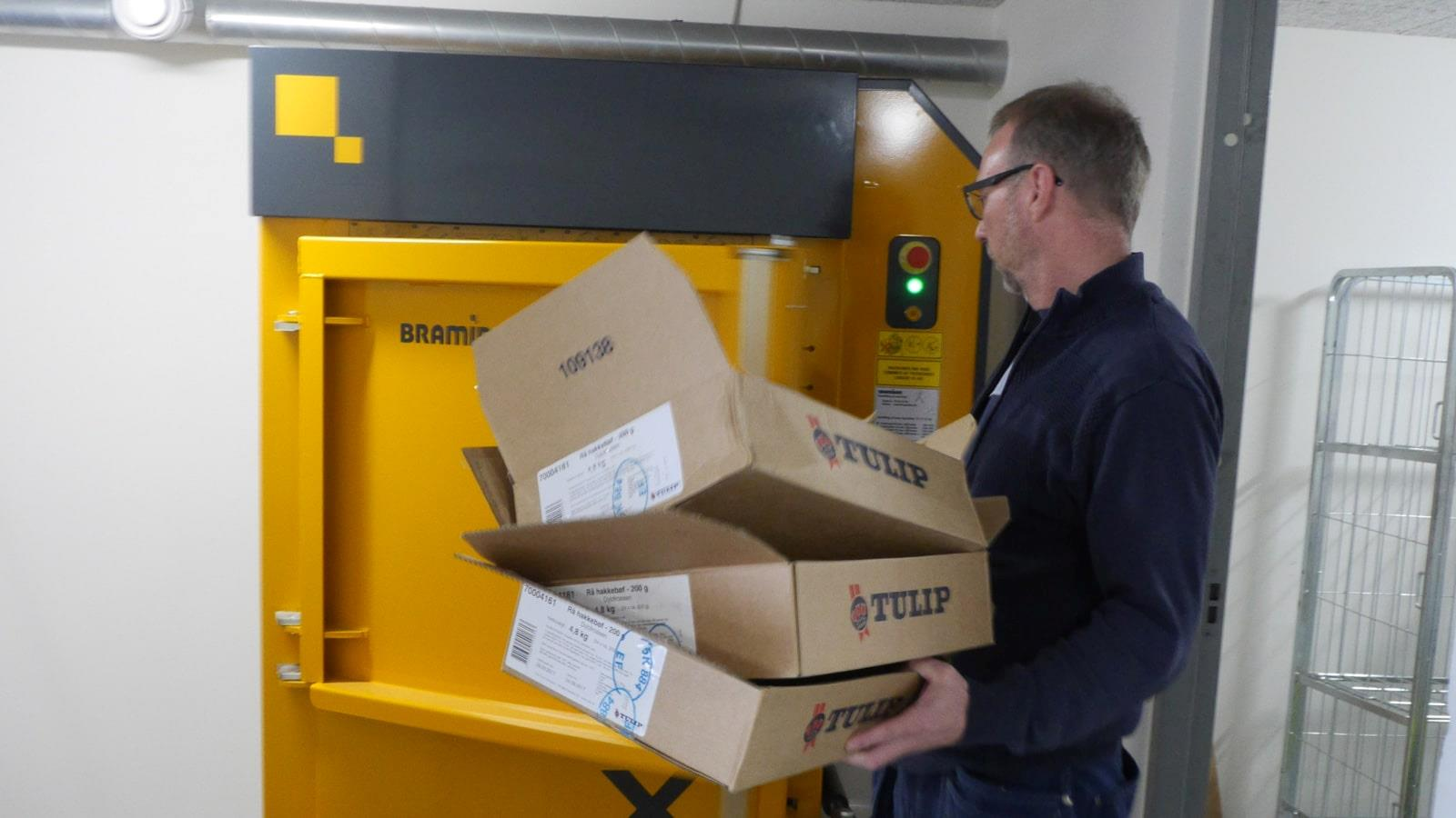 Man throwing cardboard boxes into Bramidan X10 baler