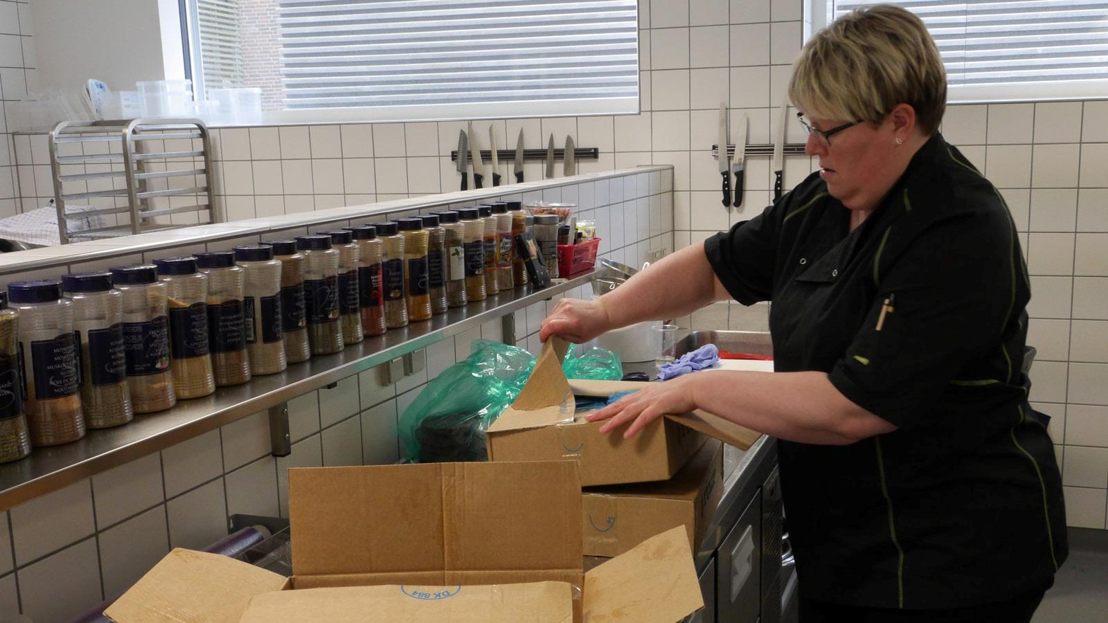 Canteen employee opening cardboard boxes with Tulip meat products