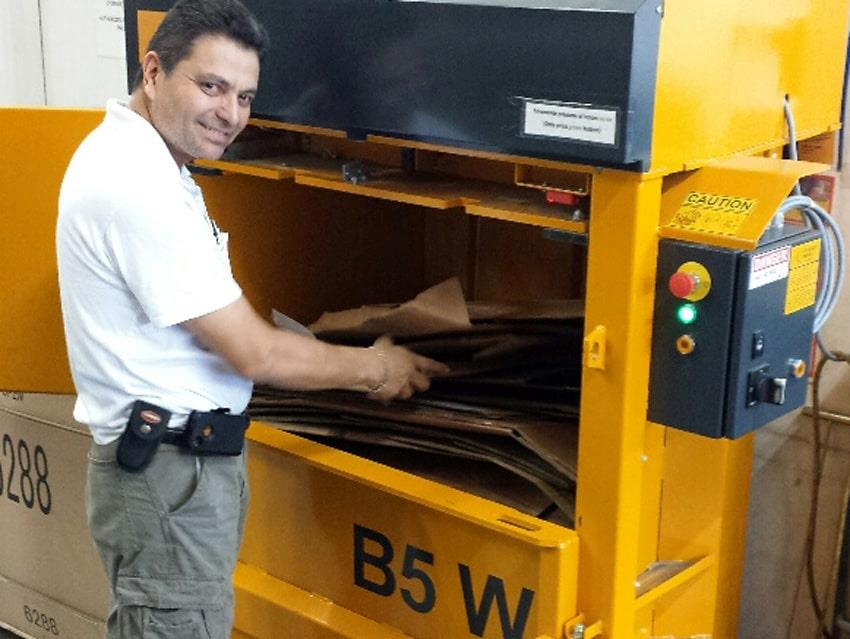 Man fills cardboard waste into B5 Wide Bramidan baler