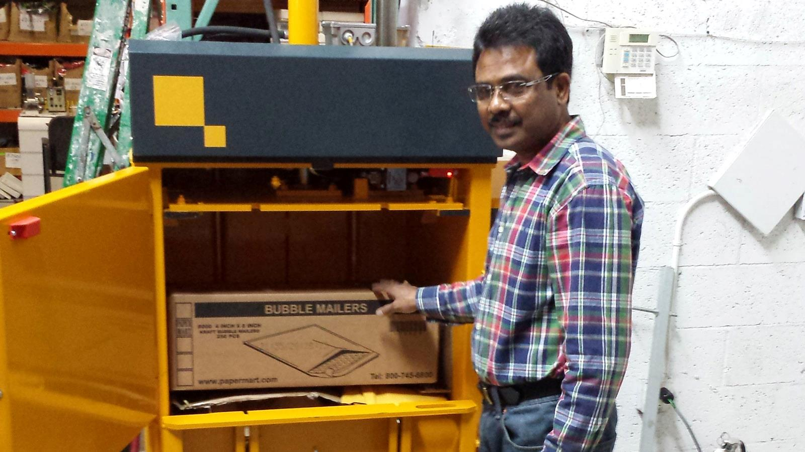 Employee at Marshall Wallets fills cardboard into small Bramidan baler