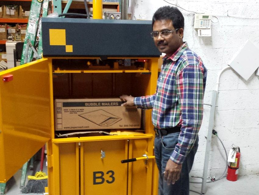 Man in chequered shirt fills cardboard into Bramidan baler B3