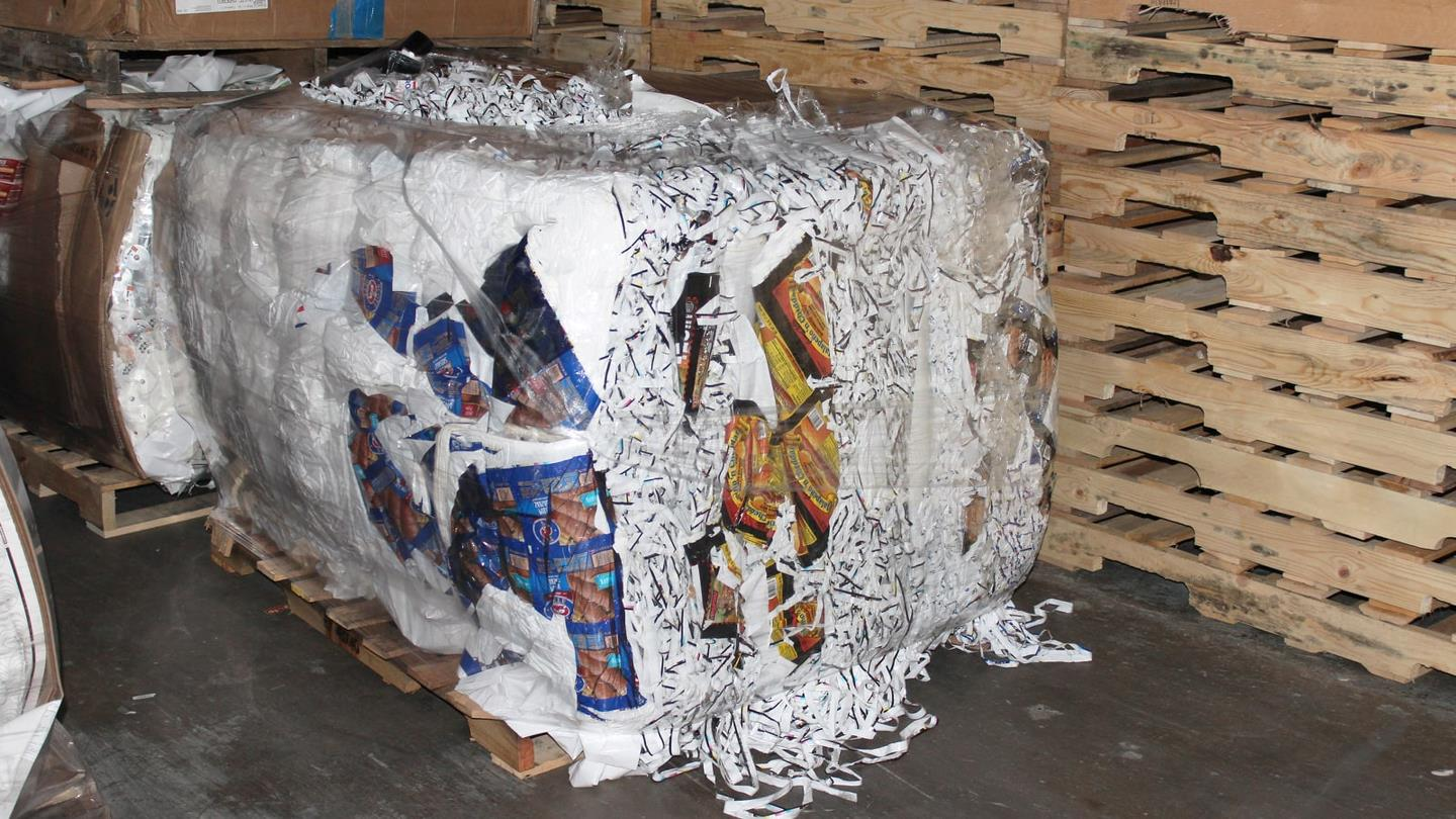Compacted bale of shredded plastic placed on a pallet