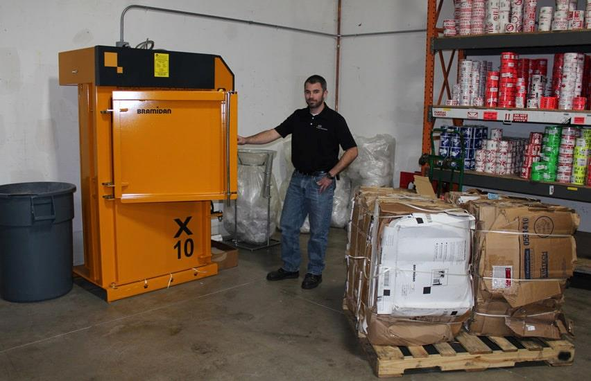 Man next to X10 baler and two cardboard bales