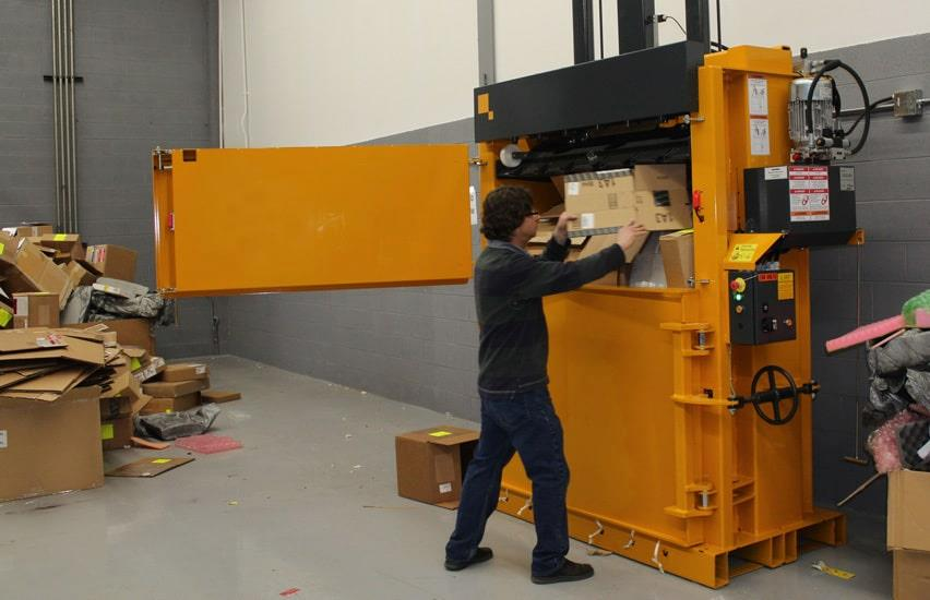 Man fills cardboard waste into yellow baler