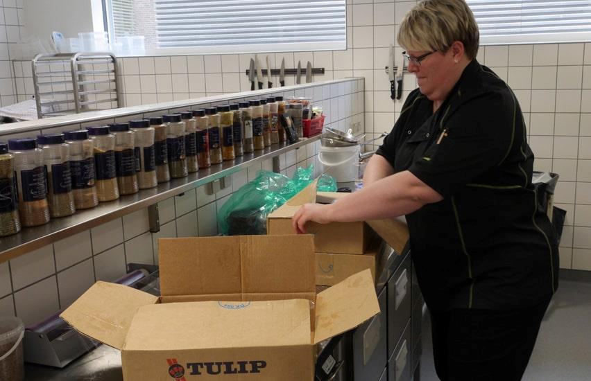 Woman unpacking food in canteen