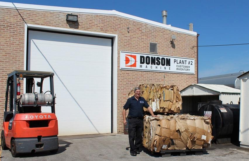 Man next to cardboard bales at Donson Machine