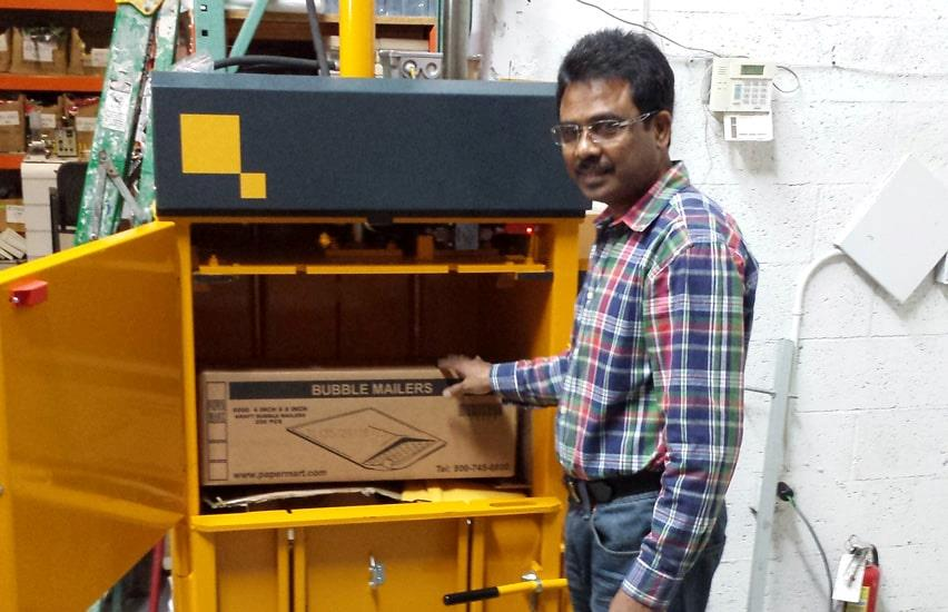 employee fills cardboard into B3 stockroom baler