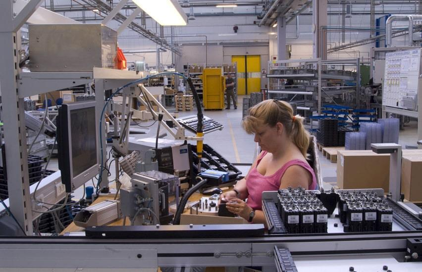 Woman in pink at assembly line at Sauer Danfoss