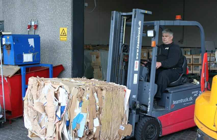 Man moves cardboard bale with forklift truck