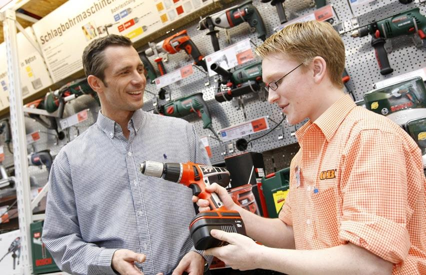 OBI employee explains to customer about a drilling machine