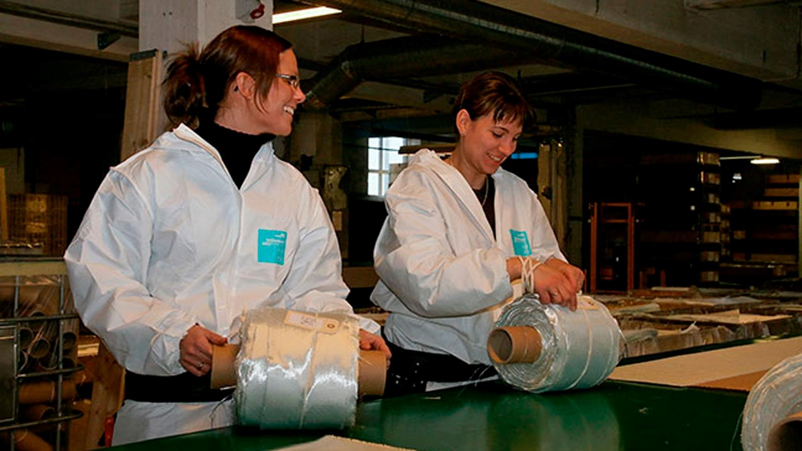 Two female employees at RewAir put labels on glass fibre rolls