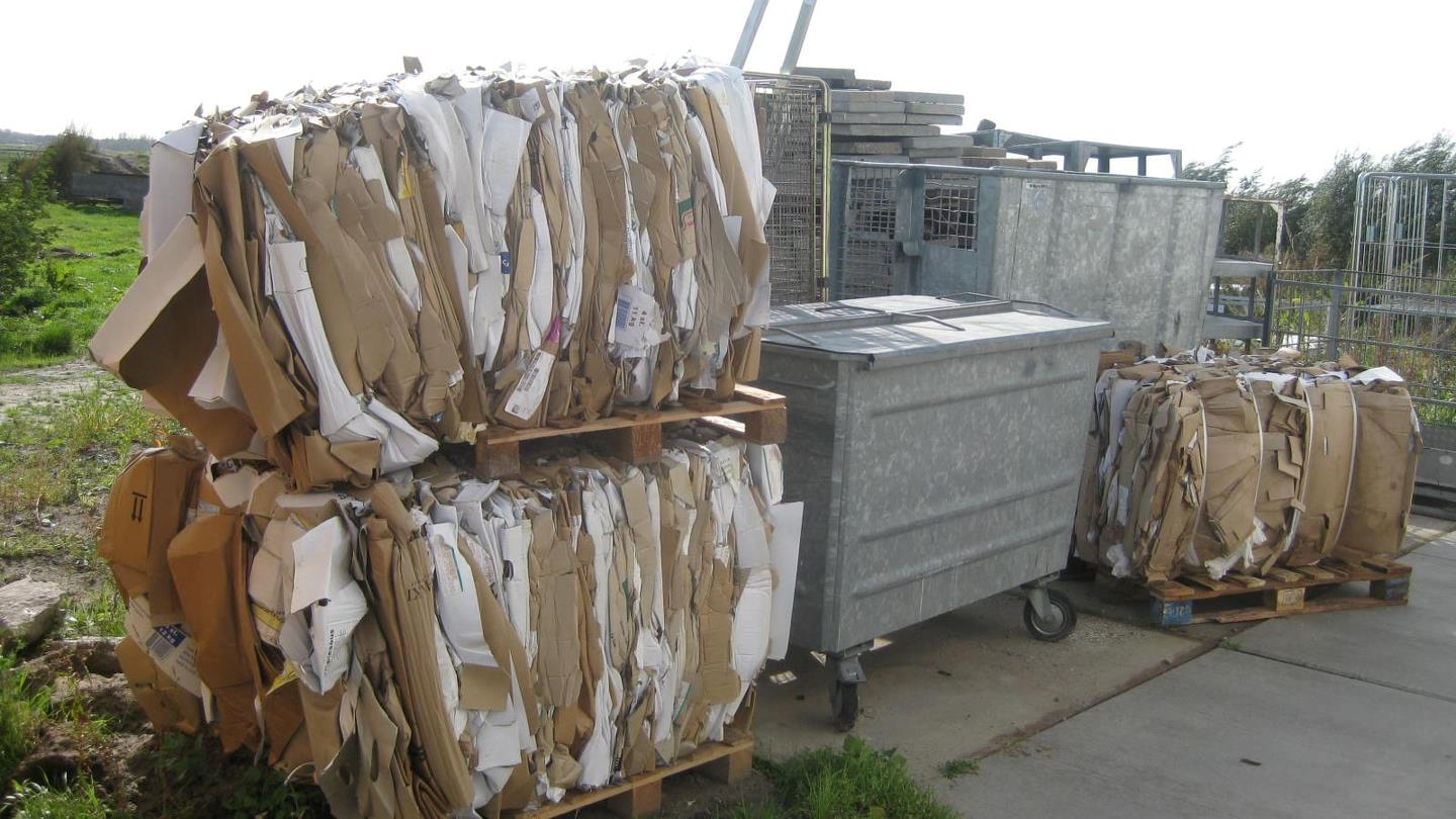 Finished bales of cardboard outside