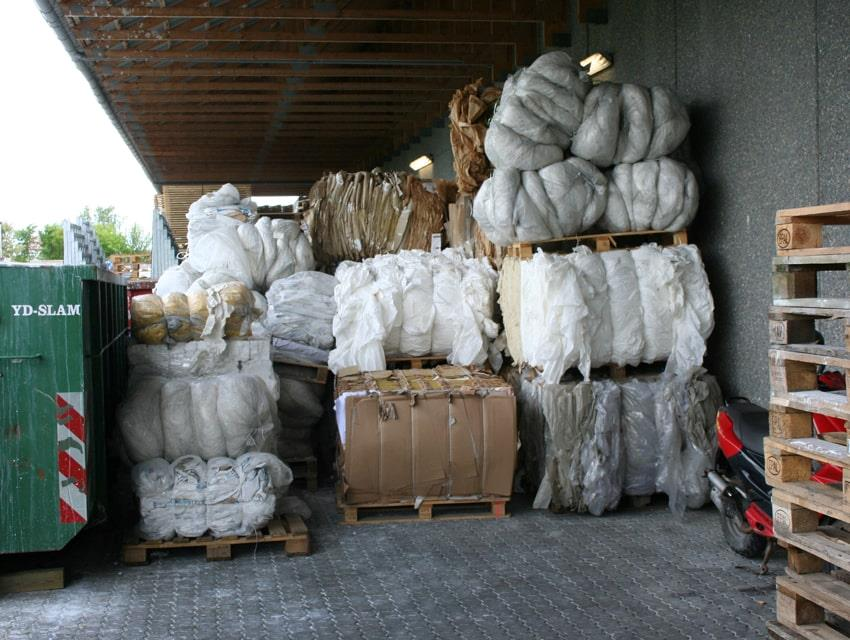 Cardboard and plastic bales stacked outside under shelter