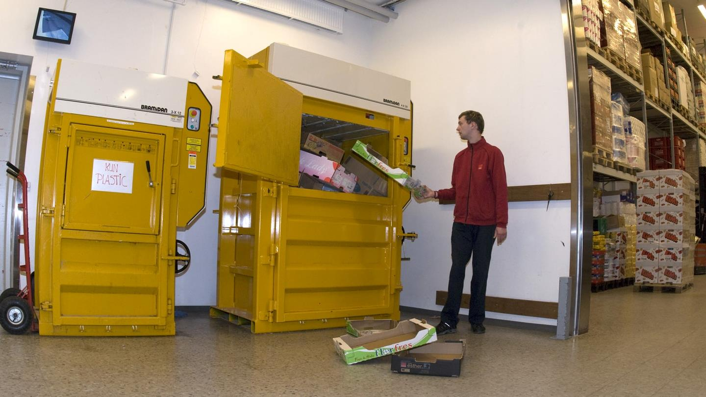 In the backroom storage man fills Bramidan baler with cardboard