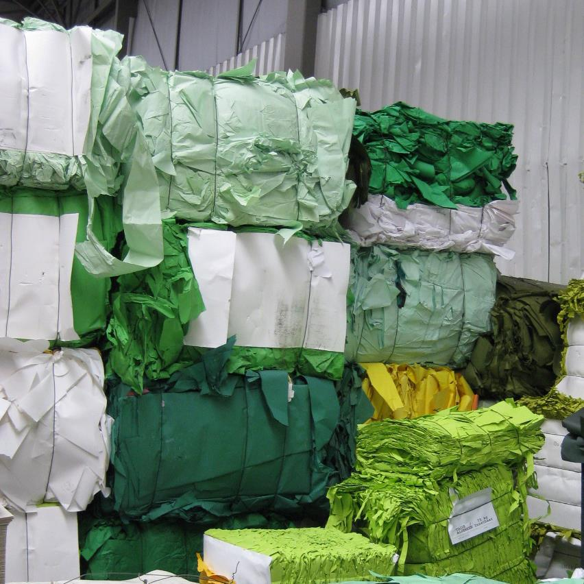 Green coloured paper waste compacted into bales