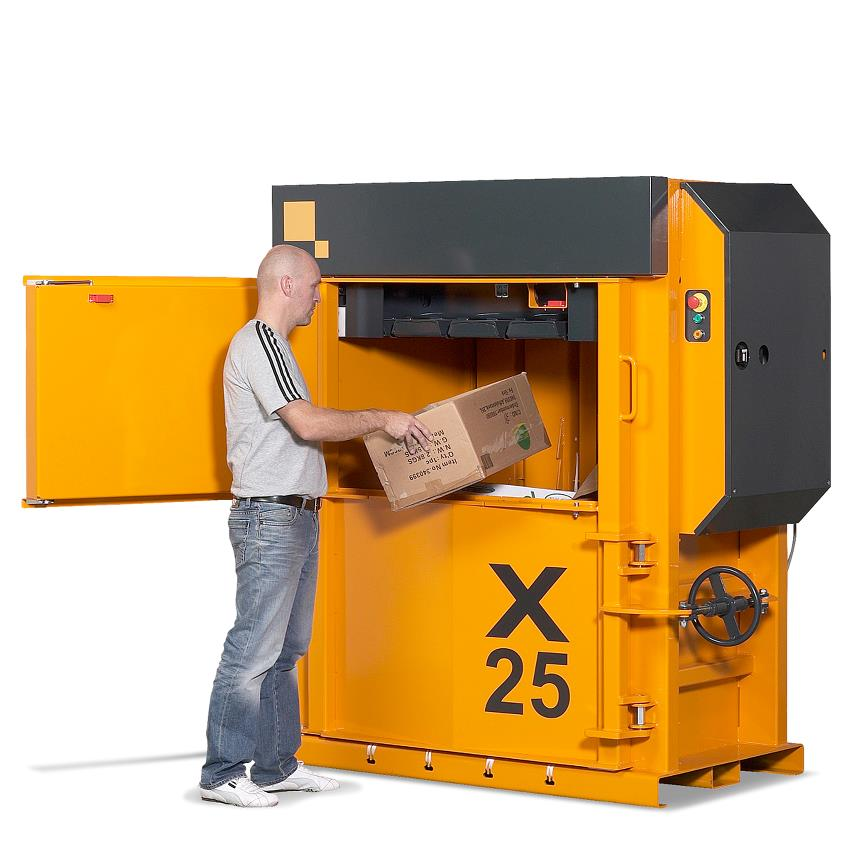 Man puts cardboard waste into X25 HD baler from Bramidan