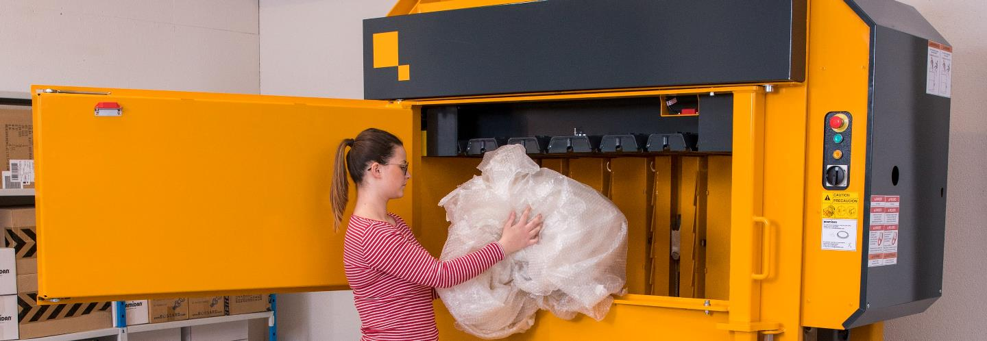 Girl fills plastic waste into Bramidan Baler X6030 with Low Profile