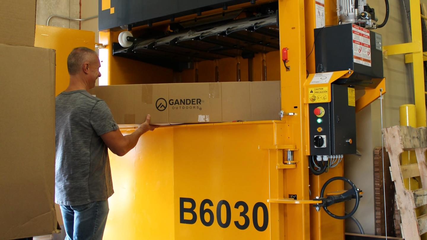 Employee at Gander Outdoors fills cardboard into Bramidan baler