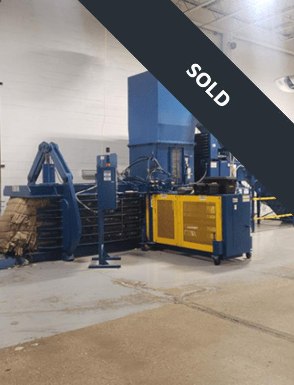 Large blue horizontal baler with boxes and yellow gate