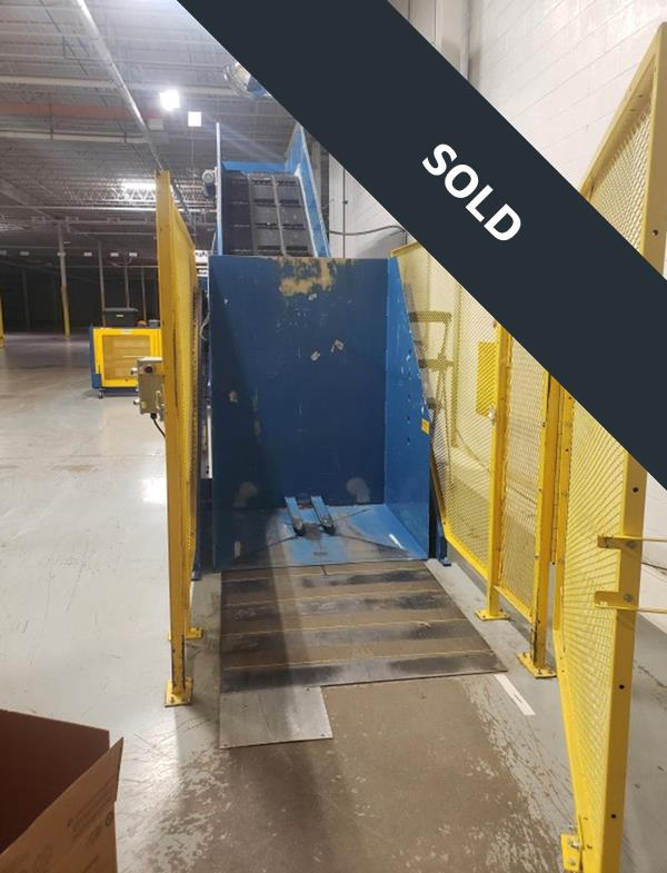Yellow gate fence on blue horizontal baler