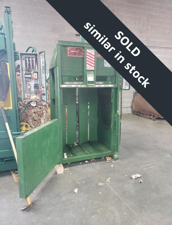 Green baler with red stickers and open door in front of boxes