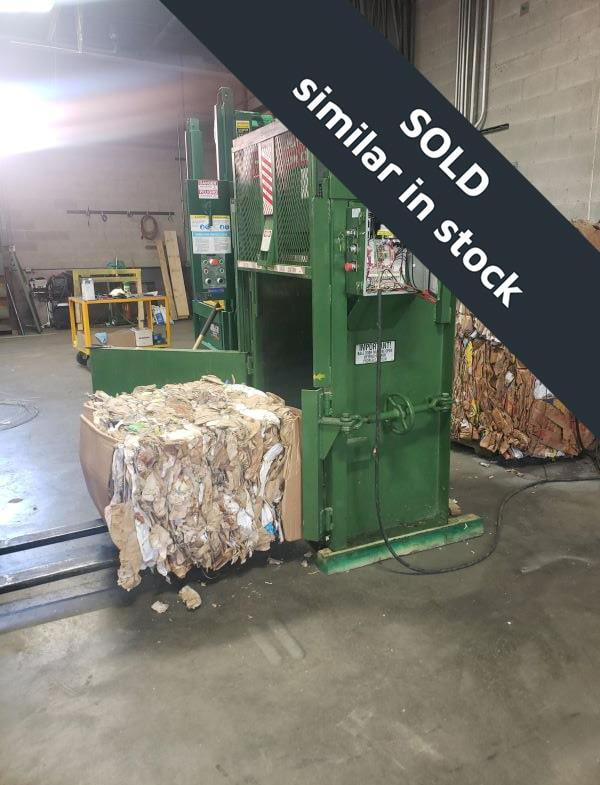 Green baler with open door and bale of cardboard