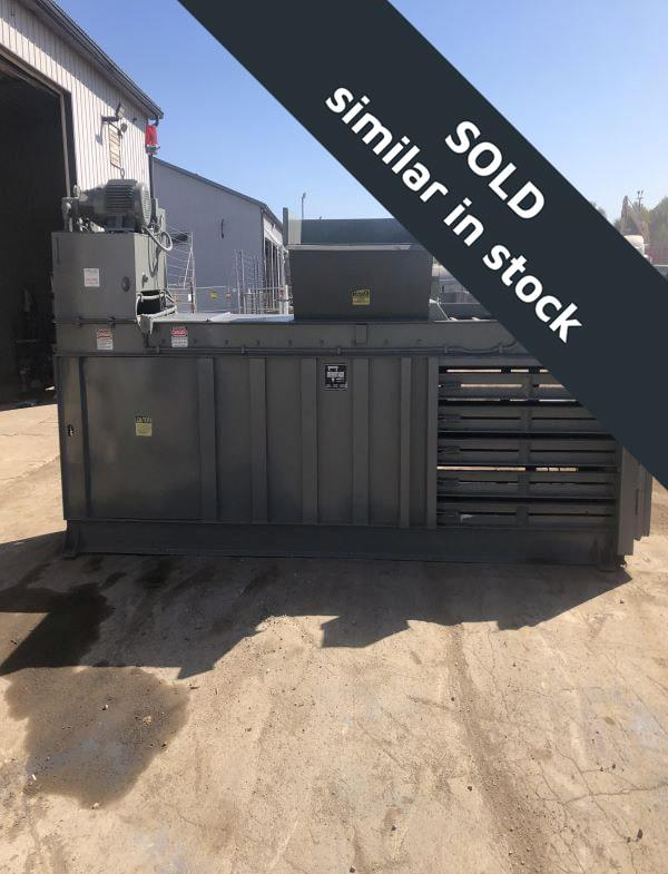 Brown horizontal baler in parking lot