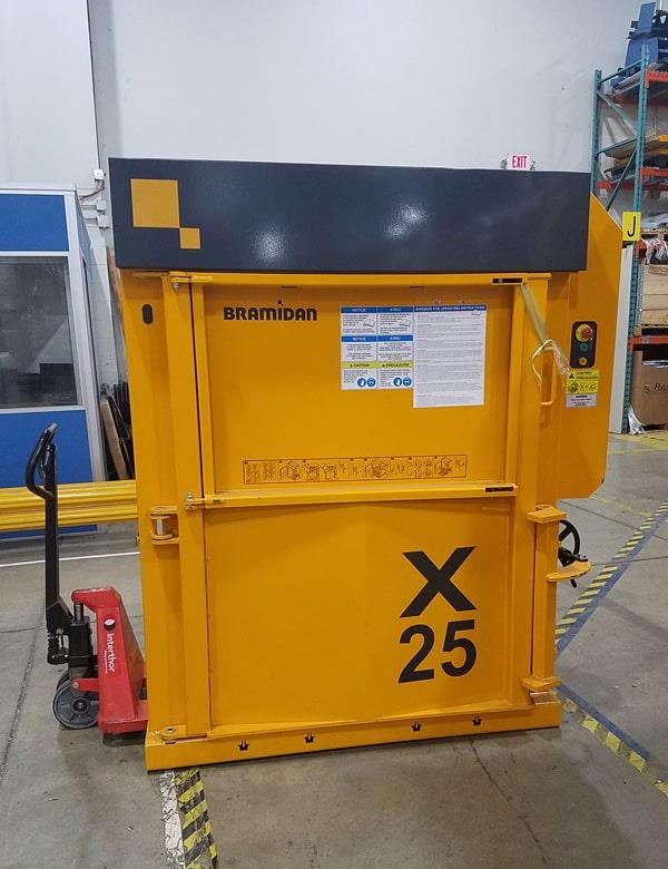 Low profile yellow baler on pallet jack in warehouse