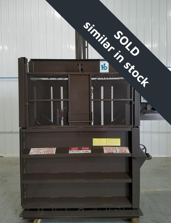 Front view of brown vertical baler sitting inside shop