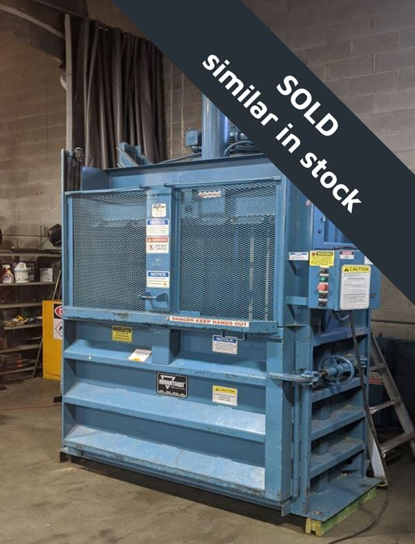 Blue baler with closed gate and yellow stickers