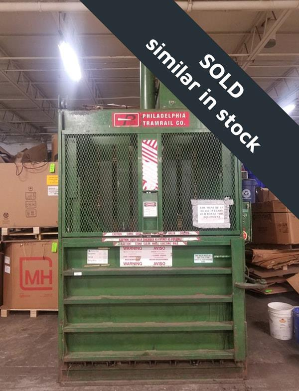 Green vertical baler in front of boxes inside back stockroom