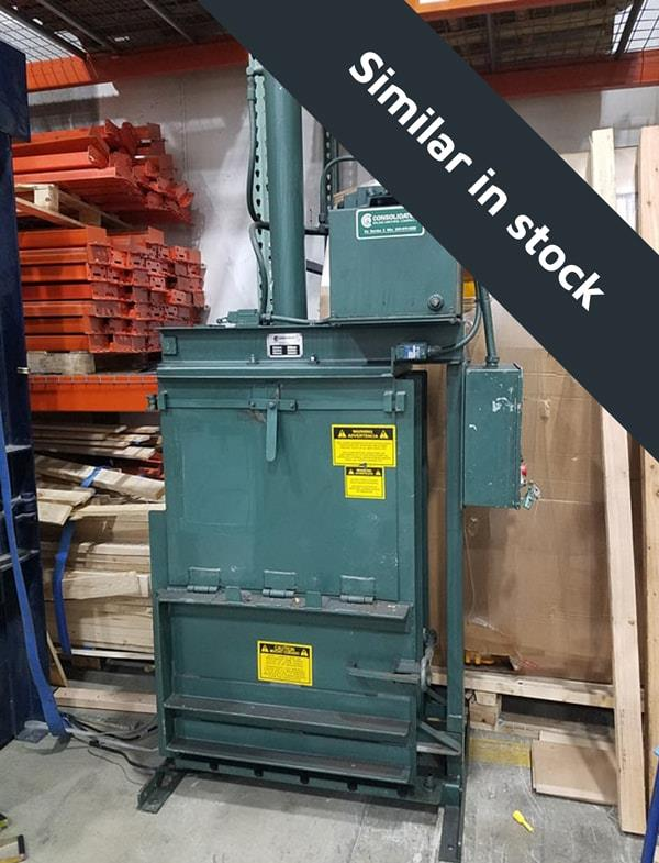Small green baler sits under racking in warehouse