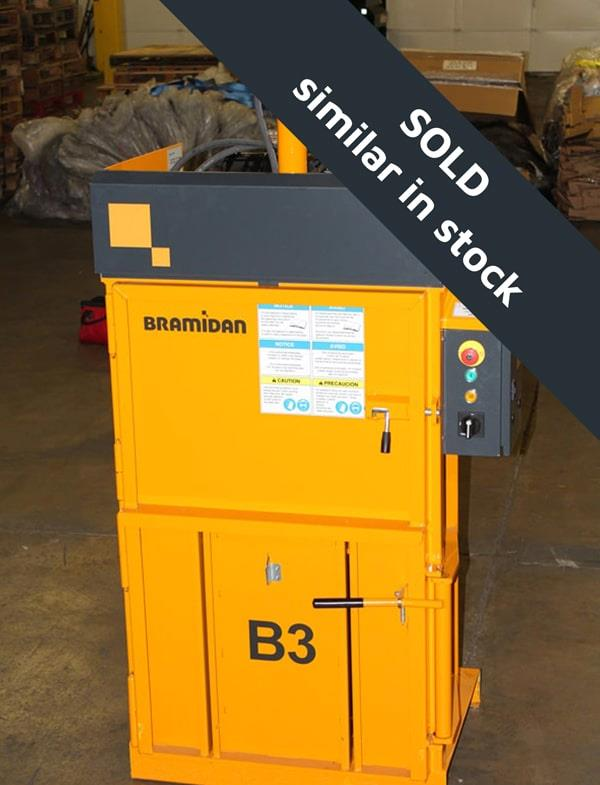 Front view of small yellow vertical baler in warehouse